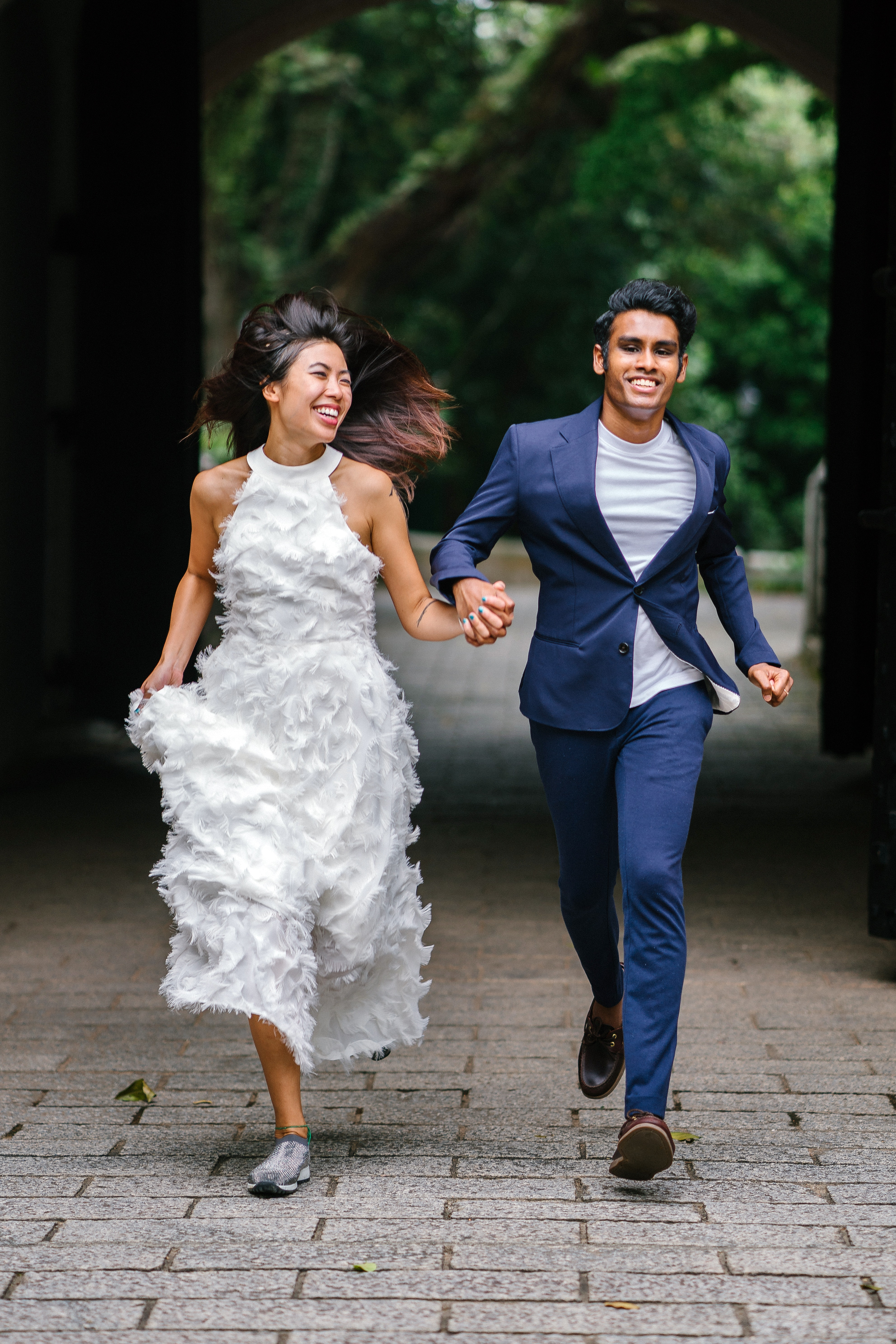 Happy bride in wedding gown and groom in blue suit running while holding hands on their wedding day.