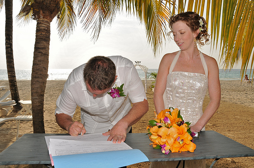 destination wedding tropical couple signing marriage contract on the beach.