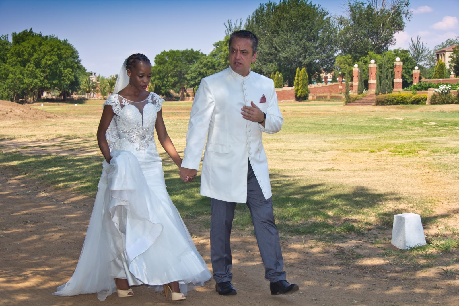 phindi walking. International bride with groom on their wedding day.
