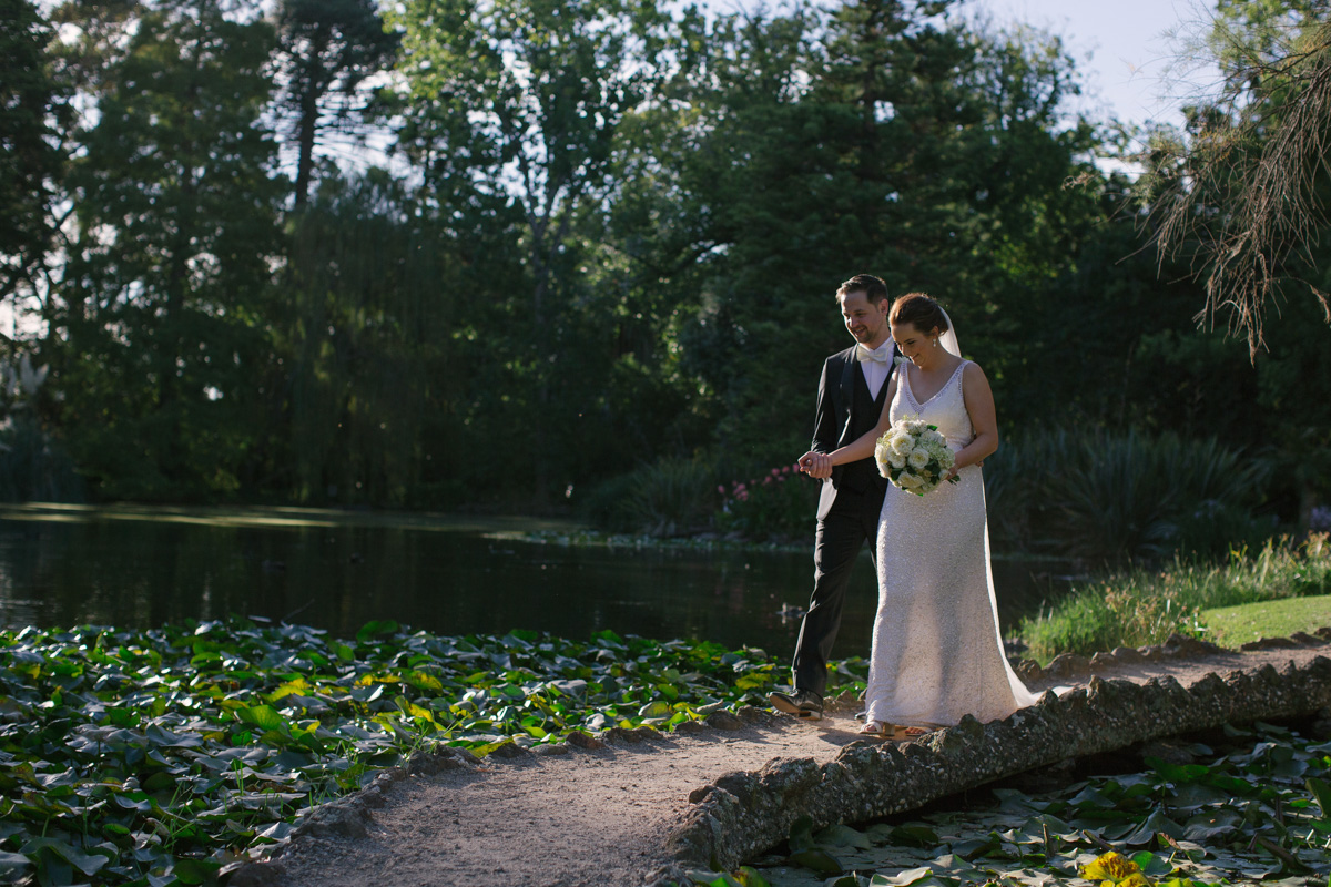 Real bride Jacinta on her wedding day, strolling through a lush forest with her groom.