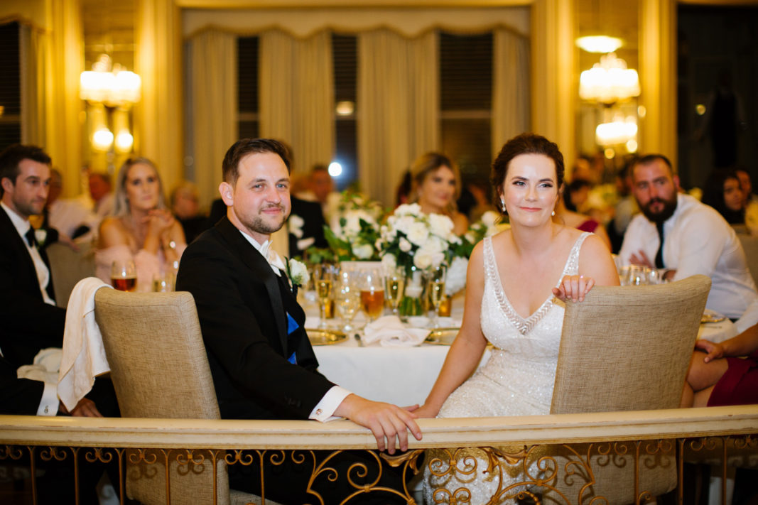 Real Bride Jacinta with groom sitting at the wedding party table and enjoying listening to wedding speeches.