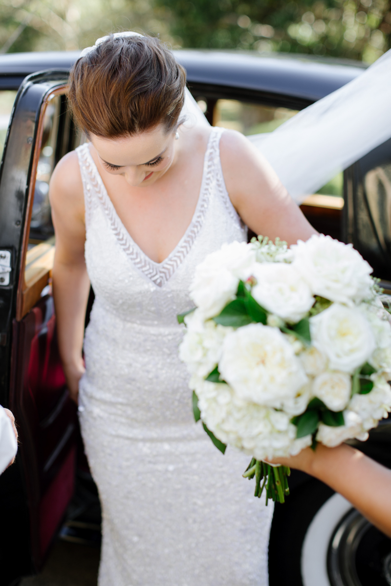 Real Bride Jacinta in her wedding dress and with bridal bouquet in hand.