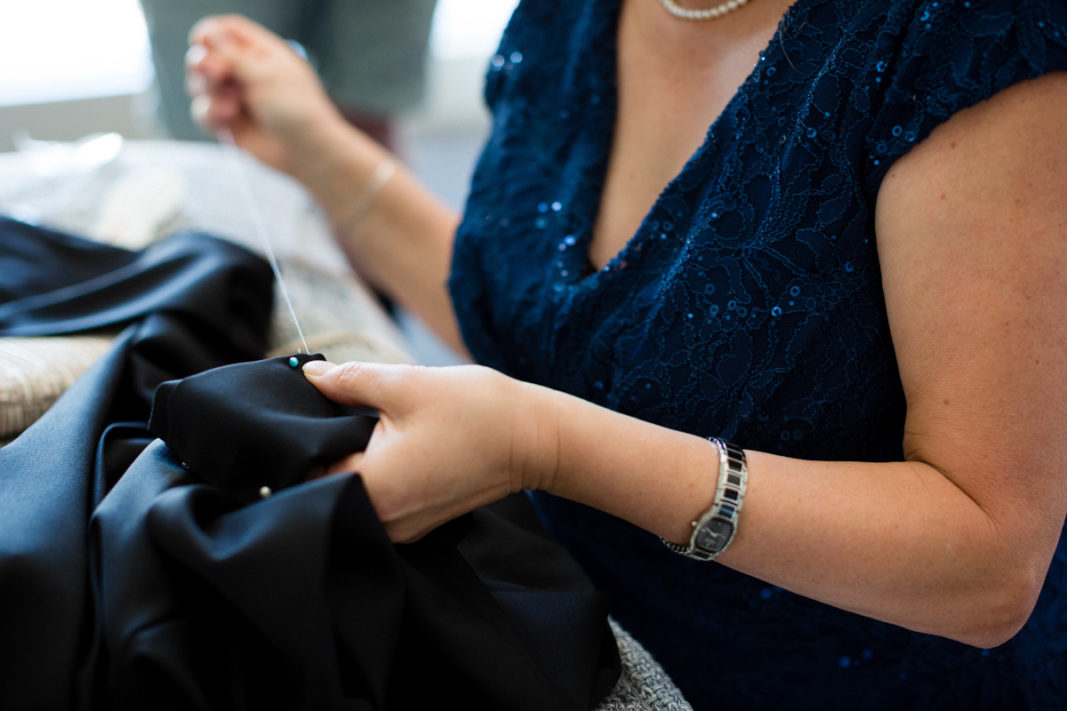 A closeup of the Real Bride groom's mother sewing up formal pants before the wedding ceremony.