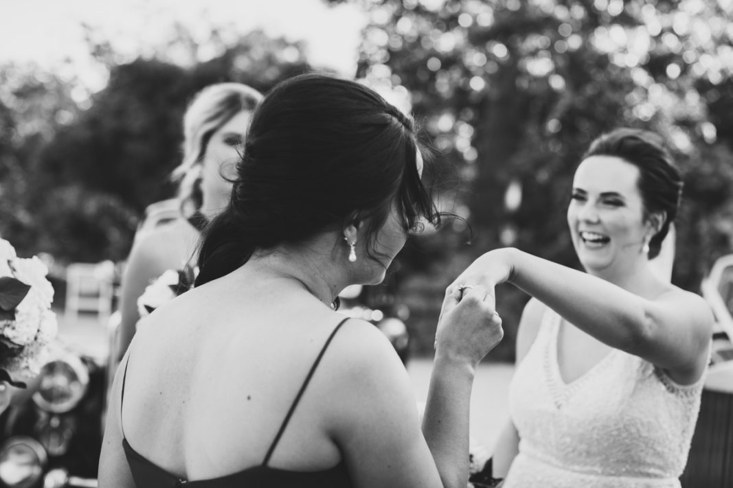Black and white photo of AWGS Real Bride Jacinta showing off her engagement ring to her bridesmaids.